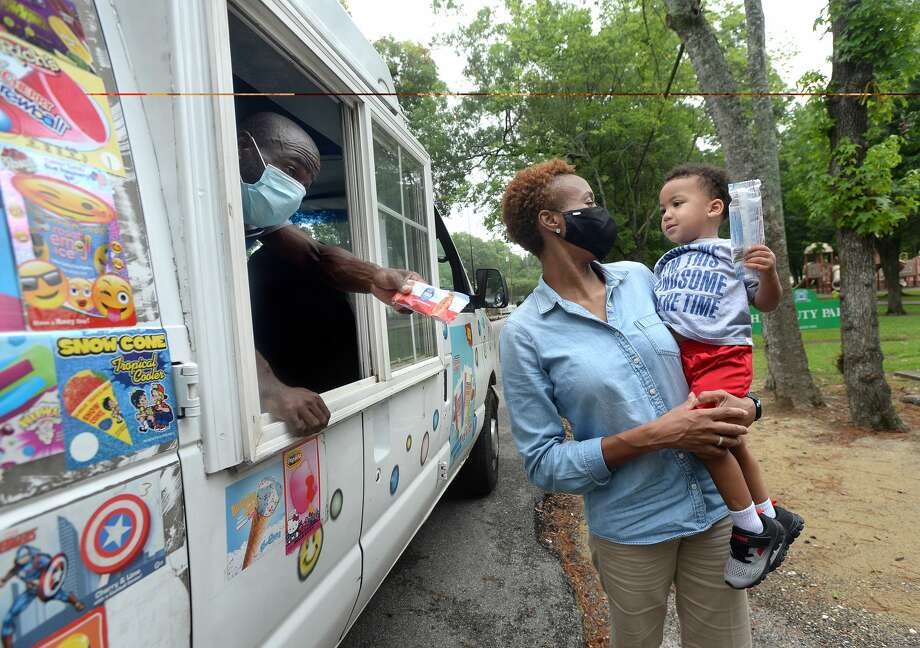 Homer Drive Elementary Principal Dr. Belinda George shares a moment with Cameron Flowers after getting him ice cream as Doyle Payia offers others treats from the window of his ice cream truck as she and others travel through the neighborhoods surrounding the school, passing out cool treats to kids Friday. This is the second annual Popsicles from the Principal event she has held. Although turnout was lower than the 600-some treats they had to distribute, which she attributed to a combination of the weather and COVID-19, it was still a good opportunity to see the students again and connect while school is out for the summer, she said. Photo taken Friday, June 26, 2020 Kim Brent/The Enterprise Photo: Kim Brent/The Enterprise