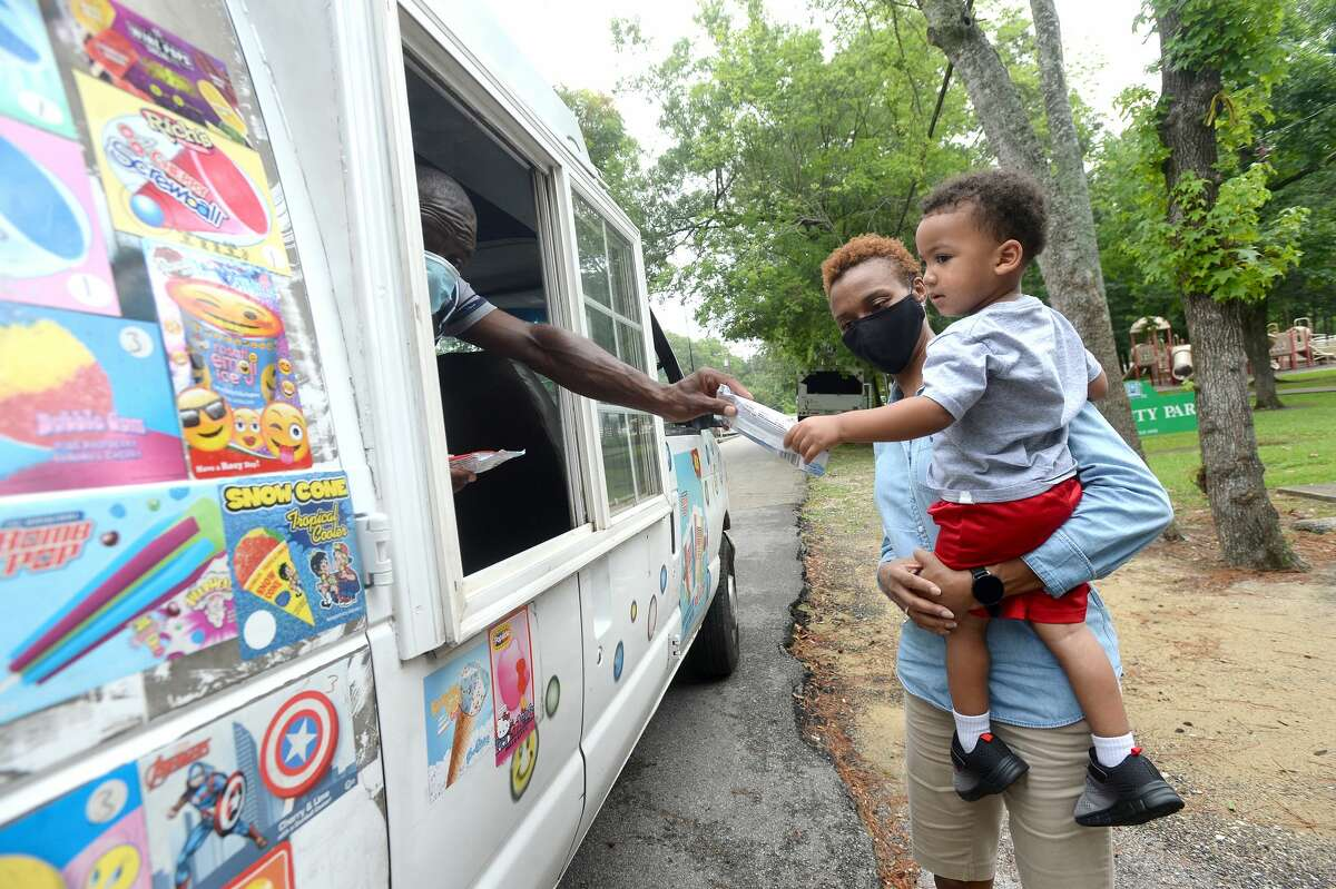 Homer Drive Elementary Principal Dr. Belinda George holds Cameron Flowers as he gets a treat from Doyle Payia as she and others travel through the neighborhoods surrounding the school, passing out cool treats to kids Friday. This is the second annual Popsicles from the Principal event she has held. Although turnout was lower than the 600-some treats they had to distribute. which she attributed to a combination of the weather and COVID-19, it was still a good opportunity to see the students again and connect while school is out for the summer. While making their way through several stops, roadworkers along the route also received popsicles and ice cream. Photo taken Friday, June 26, 2020 Kim Brent/The Enterprise