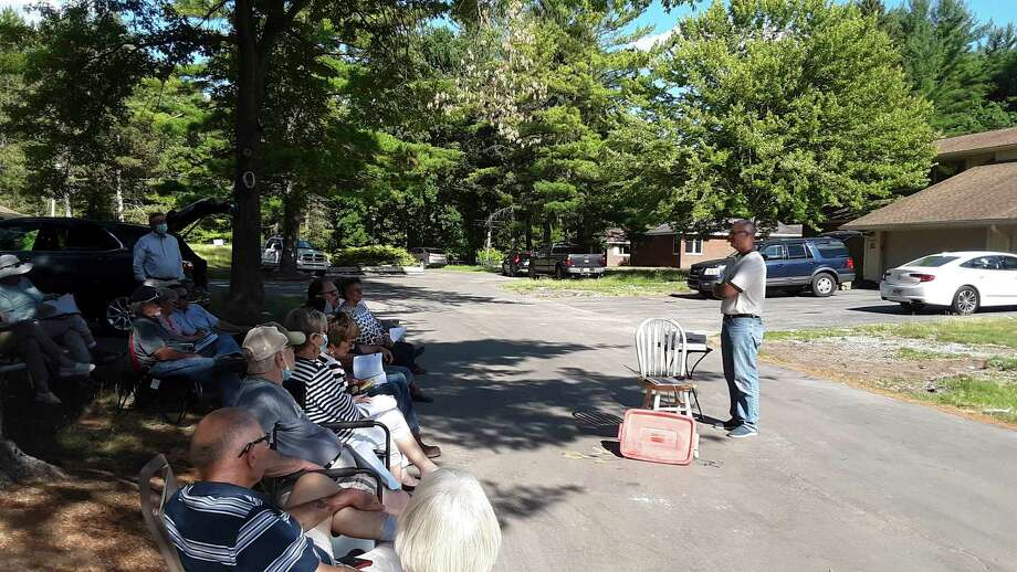 Doug Loose, right, speaks to residents of Village West Condominiums during an outdoor meeting on Thursday evening, where he presented a proposal to purchase their flooded residences, restore them and rent them to the residents at a discounted rate. (Dan Chalk/chalk@mdn.net)