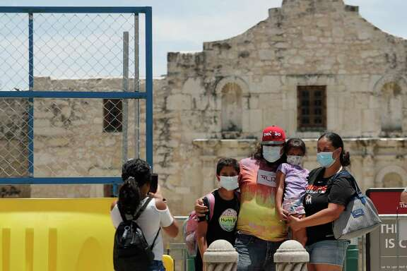 Visitors wearing masks to protect against the spread of COVID-19 pose last week at the Alamo, which remains closed. Cases of COVID-19 have spiked in Texas.  Readers say Gov. Greg Abbott and President Donald Trump have failed in their response to the pandemic.