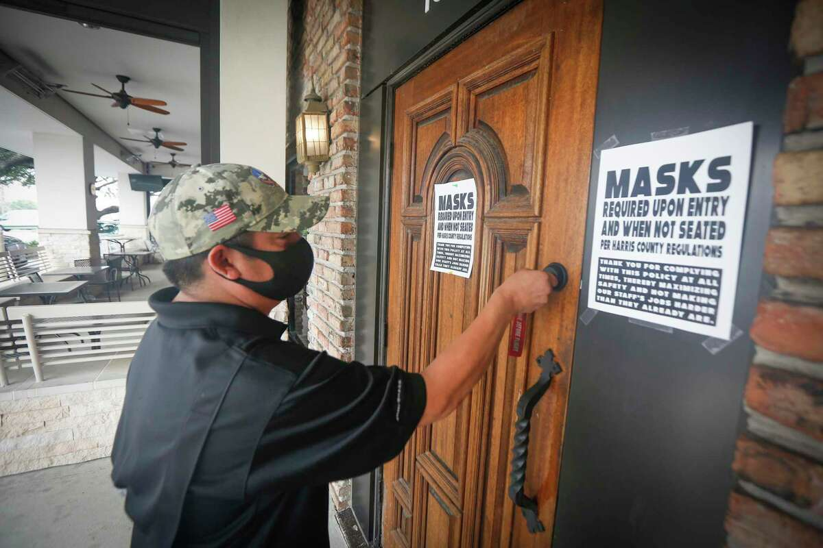 Ron's Bar Assistant Manager Howard McElroy locks the entrance at noon, as Gov. Greg Abbott's order to shut down all bars in Texas became in to effect Friday, June 26, 2020, in Houston.