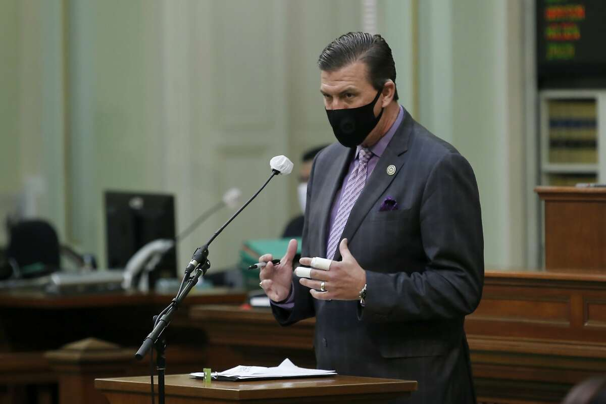 Assemblyman Kevin Mullin, D-South San Francisco, wears a face mask as he urges lawmakers to approve a measure to place a proposed constitutional amendment on the ballot to allow state legislators to vote remotely during emergencies, at the Capitol in Sacramento, Calif., on Wednesday, June 10, 2020. The Assembly approved the measure and it sent it to the Senate which has until June 25 to pass the proposal and place it before voters in November. (AP Photo/Rich Pedroncelli)