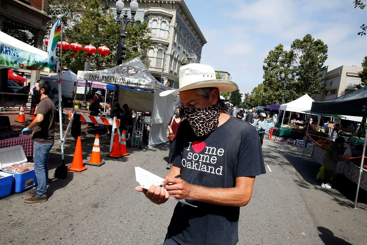 Josh Assink, operations manager for Urban Village Farmers� Market Associates, checks paperwork whle working at the Old Oakland Farmers� Market on Friday, June 26, 2020 in Oakland, Calif.