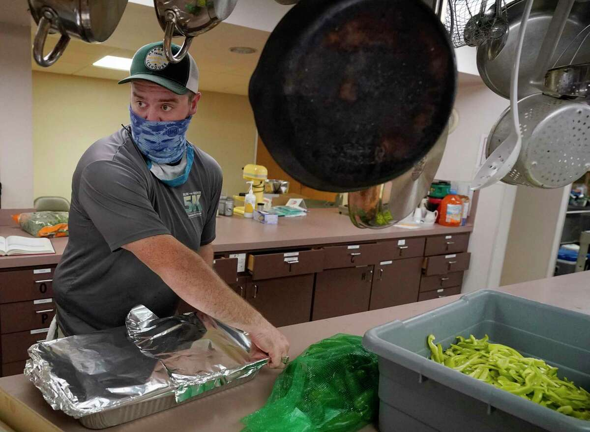 Lucas Marr works in the kitchen of St. Stephen's United Methodist Church, 2003 W. 43rd St., as he and Rev. Nathan Lonsdale Bledsoe prepare food as part of Furlough Kitchen Houston Thursday, June 18, 2020, in Houston. Furlough Kitchen Houston offers free meals by reservation for curbside pick-up. So far, the church has provided about 1,400 free meals to the community.