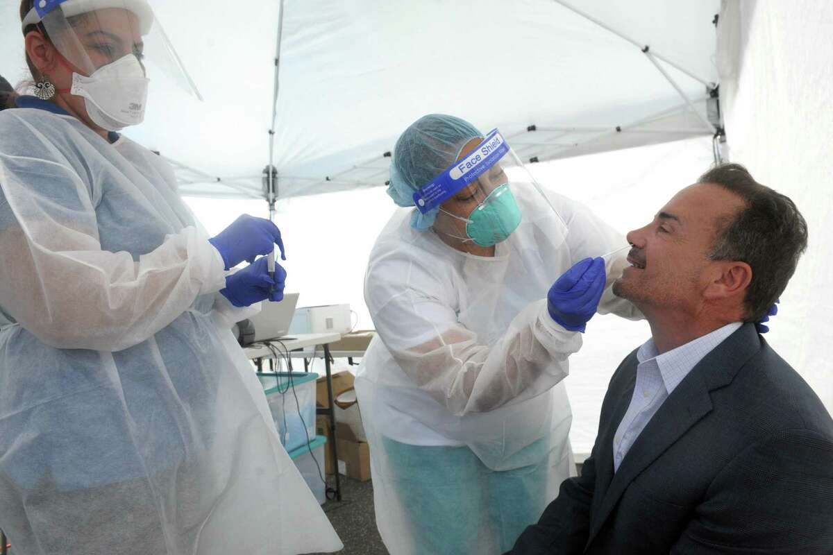 Bridgeport Mayor Joe Ganim sits for a COVID-19 test during a visit to the mobile testing site set up outside Mount Aery Baptist Church, in Bridgeport, Conn. June 26, 2020. Ganim is seen here with Optimus Health Care medical assistants Dolimar Rivera, center, and Cassandra Rodriguez, left.