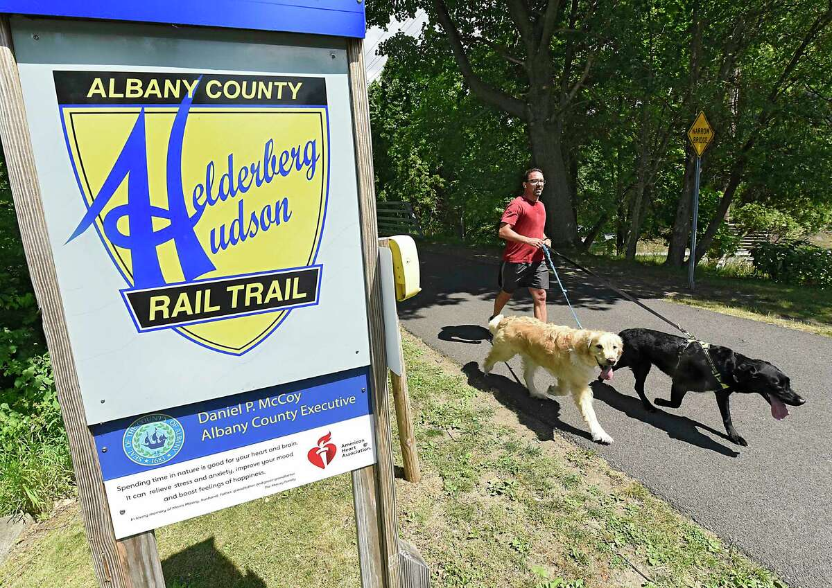 A man runs with his dogs along the Albany County Helderberg-Hudson Rail Trail on Friday, June 26, 2020 in Delmar, N.Y. Albany County Executive Daniel McCoy announced that for the first time, food and refreshment vendors will be able to sell their products along the nine-mile stretch of the Albany County Helderberg-Hudson Rail Trail through food trucks, carts or temporary stands. (Lori Van Buren/Times Union)