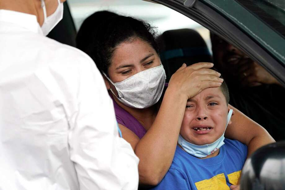 Lillian Palacios, center, holds her son, Daniel, 7, as a healthcare professional prepares to take a sample. Photo: David J. Phillip, STF / Associated Press / Copyright 2020 The Associated Press. All rights reserved.