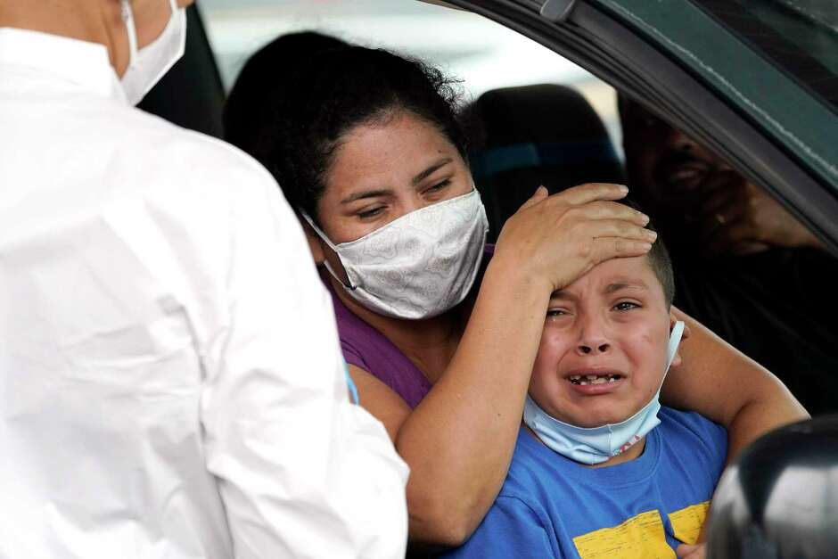 "Lillian Palacios, center, holds her son, Daniel, 7, as a healthcare professional prepares to take a sample from him at a United Memorial Medical Center COVID-19 testing site Friday, June 26, 2020, in Houston. The number of COVID-19 cases continues to rise across the state. Texas Gov. Greg Abbott has said that the state is facing a ""massive outbreak"" in the coronavirus pandemic and that some new local restrictions may be needed to protect hospital space for new patients. (AP Photo/David J. Phillip)"