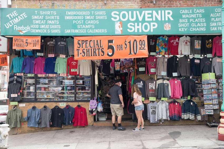 Tourists look over items for sale along Grant Ave. in San Francisco Calif. on June 26, 2020.