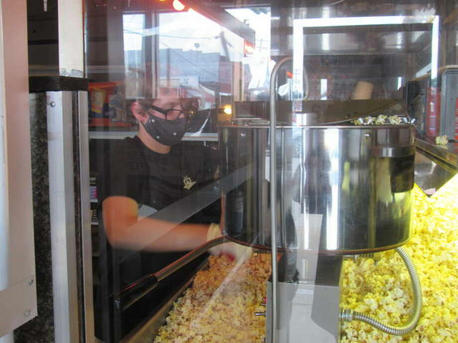 A Stadium Theater employee servies popcorn to a patron Friday evening at the Jerseyville theater's first film showings after the stay-at-home orders issued by Gov. J.B. Pritzker in mid-March.