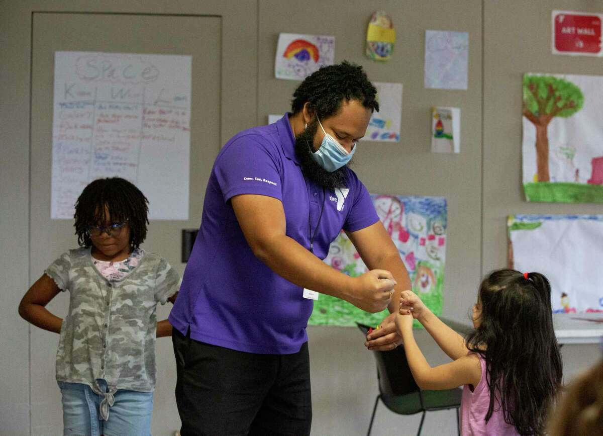 YMCA After School Counselor Kamran Assadi plays a small game with Sophia Khademi during class Tuesday, May 12, 2020, at the Weekley YMCA in Houston.