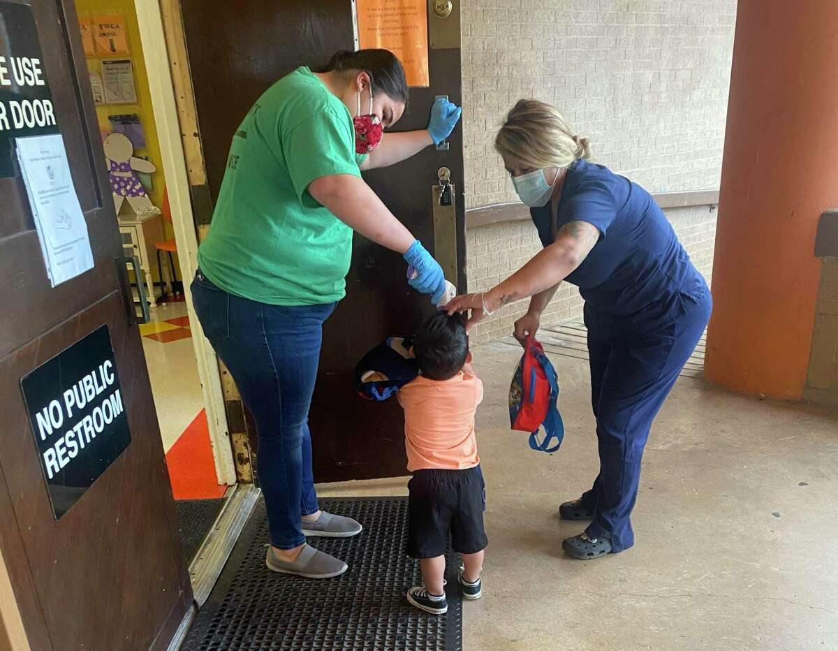 A child-care teacher at the YWCA of San Antonio checks a child's and parent's temperature as part of morning drop off.
