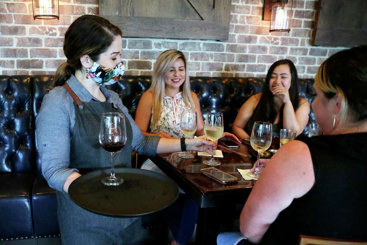 Server Kristina Garrow, left, delivers wine for a tasting to lunchtime customers at Bosscat Kitchen & Libations, a restaurant and bar on Westheimer Friday, Jun. 26, 2020 in Houston, TX. They have been operating at only 50 percent capacity since reopening the dining room June 5th.