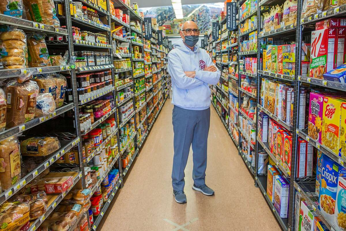 Sal Qaqundah, owner and operator of Arguello Market since 1985, explains how the new tax would effect his business while standing between the aisles on June 25, 2020.