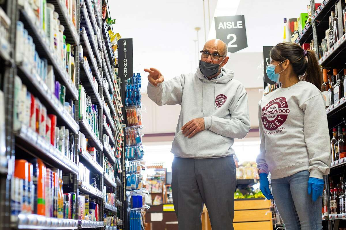 Sal Qaqundah, owner and operator of Arguello Market since 1985, shows his newest employee Xandra Gonzalez how to stock the shelves in the market on June 25, 2020.