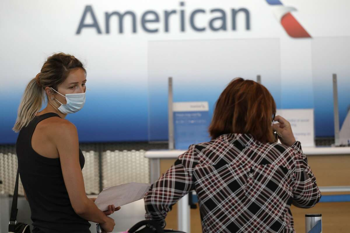 In this June 16, 2020 file photo travelers wear masks as they wait at the American Airlines ticket counter at O'Hare International Airport in Chicago.