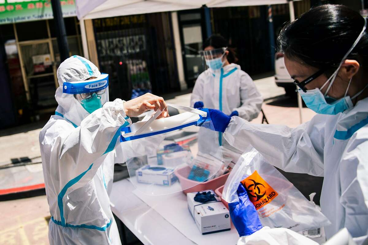 A health worker from the Chinese Hospital holds a face shield for a colleague during COVID-19 coronavirus disease testing at the Hoy Sun Ning Yung Benevolent Association on Chinatown's Waverly Place in San Francisco, Calif. on Friday, May 22, 2020.