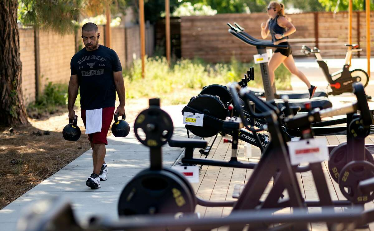 Members work out at an outdoor section of Sonoma Fitness in Petaluma, California on June 25, 2020.