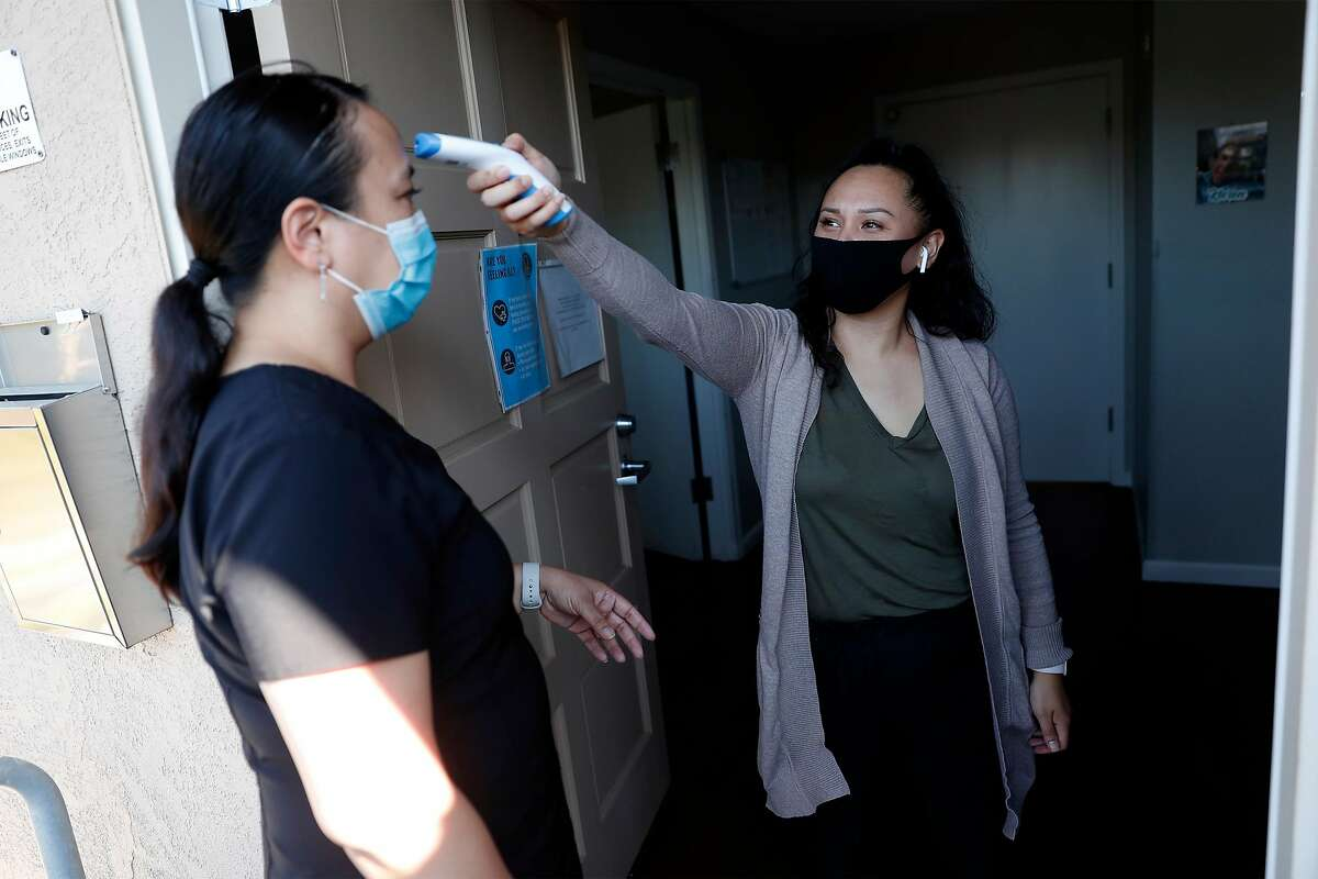 Rosalie Amacan has her temperature tested by nurse Allyssa Vergara as she arrives at Amato Home, the Fremont care home she runs.