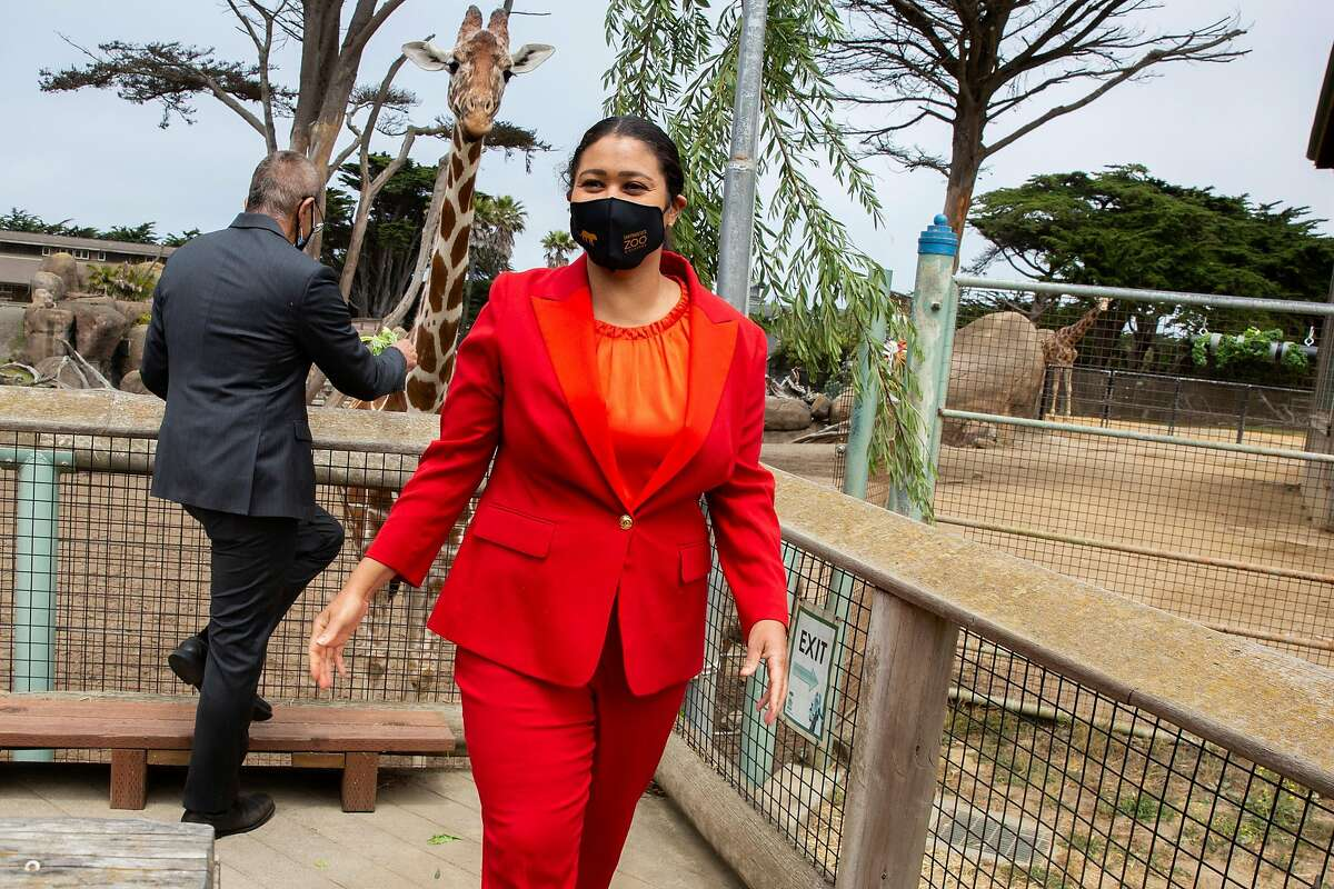 Mayor London Breed after feeding the giraffes during a tour of the San Francisco Zoo on Thursday, June 25, 2020, in San Francisco, Calif. The zoo will reopen Monday to zoo members and Wednesday to the public. Norman Yee, the president of the S.F. board of supervisors, is seen feeding a giraffe.
