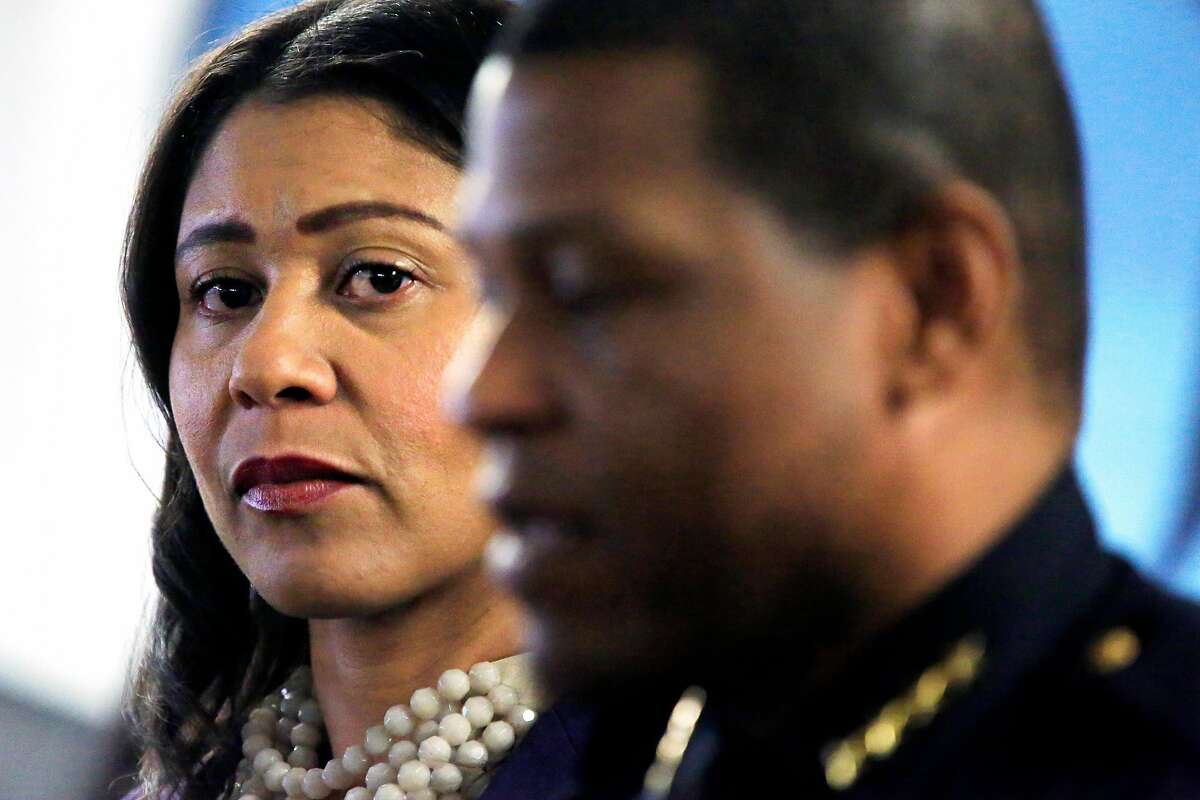 Acting Mayor London Breed (left) listens to Police Chief Bill Scott speak during a 2017 gun buy-back press conference at United Playaz in San Francisco.