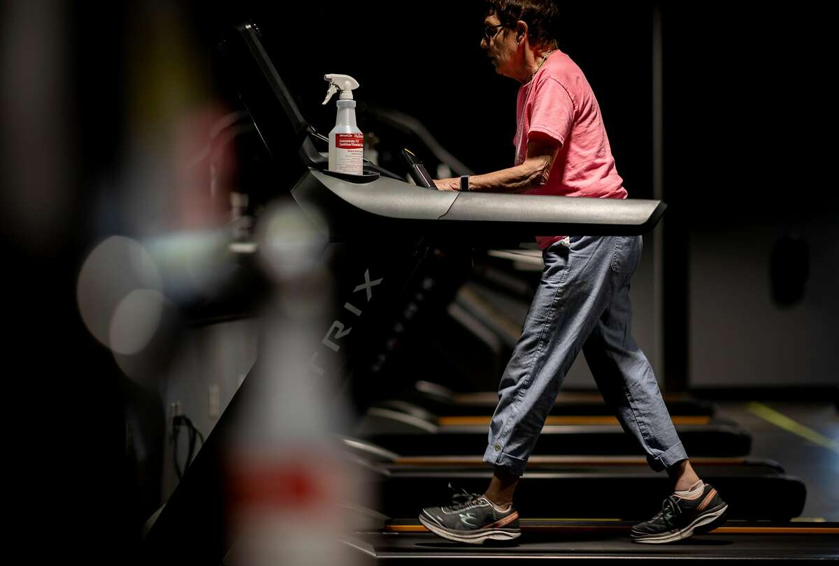 A woman walks on a treadmill at Sonoma Fitness in Petaluma, California on June 25, 2020. New safety features that include custom ventilation systems, touch-less check-in, taped off areas for social distancing and electronic pager to notify staffers that equipment has been used and must be cleaned are some of the measures local gyms employ as they begin to reopen.