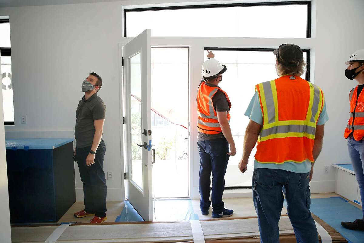 Omar Abi-Chachine (left), son of homeowner and who helped pick out the unit, checks out the�Abodu�accessory dwelling unit after it arrived to be installed on Friday, June 26, 2020 in Millbrae, Calif.