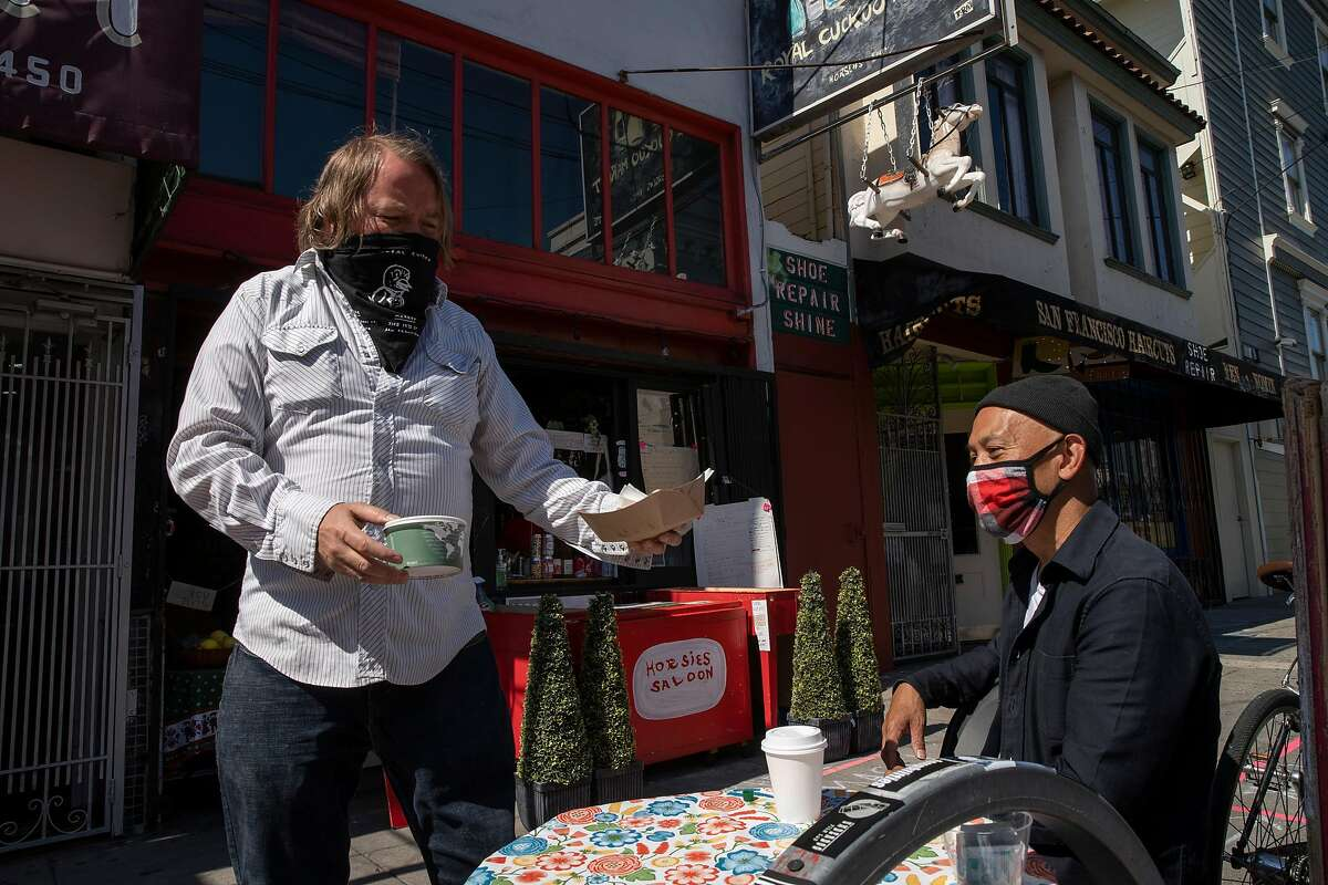 From left: Paul Miller delivers an order to Paul Valdez outside Royal Cuckoo Market on Friday, June 26, 2020, in San Francisco, Calif. San Francisco officials said Friday that the city was delaying plans to allow certain businesses � including nail salons, museums and outdoor bars � to reopen Monday following a spate of new COVID-19 cases. Coronavirus cases in California and across the country have spiked in recent weeks, largely following efforts to reopen the economy and allow people to move around more freely.