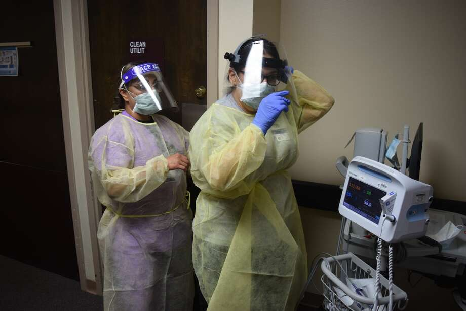 Above, Veronica Rosales, CAN, helps Deidre Enriquez, LVN tie her Personal Protective Equipment as caregivers at Covenant Health Plainview work during the COVID-19 pandemic. Photo: Provided By Covenant Health Plainview