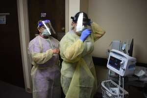 Above, Veronica Rosales, CAN, helps Deidre Enriquez, LVN tie her Personal Protective Equipment as caregivers at Covenant Health Plainview work during the COVID-19 pandemic.