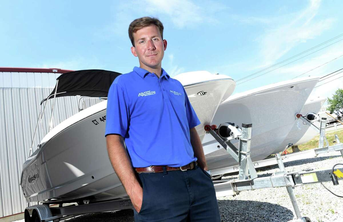Atlantic Outboard sales manager Evan Cusson is photographed by some of their remaining boats at the Westbrook business on Friday.