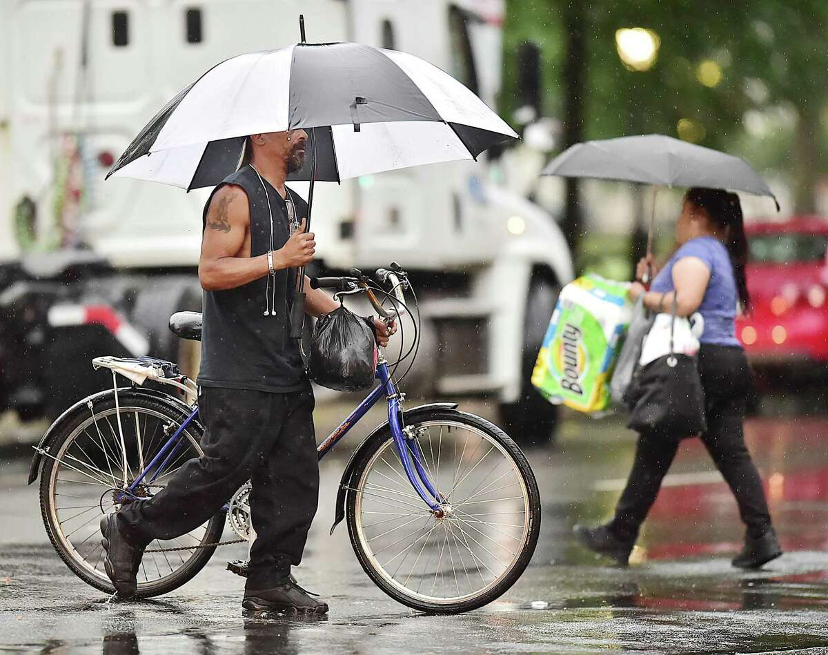 A cyclist and a pedestrian across Church Street as the skies grew dark during thunderstorms, Tuesday afternoon, July 17, 2018 in New Haven.