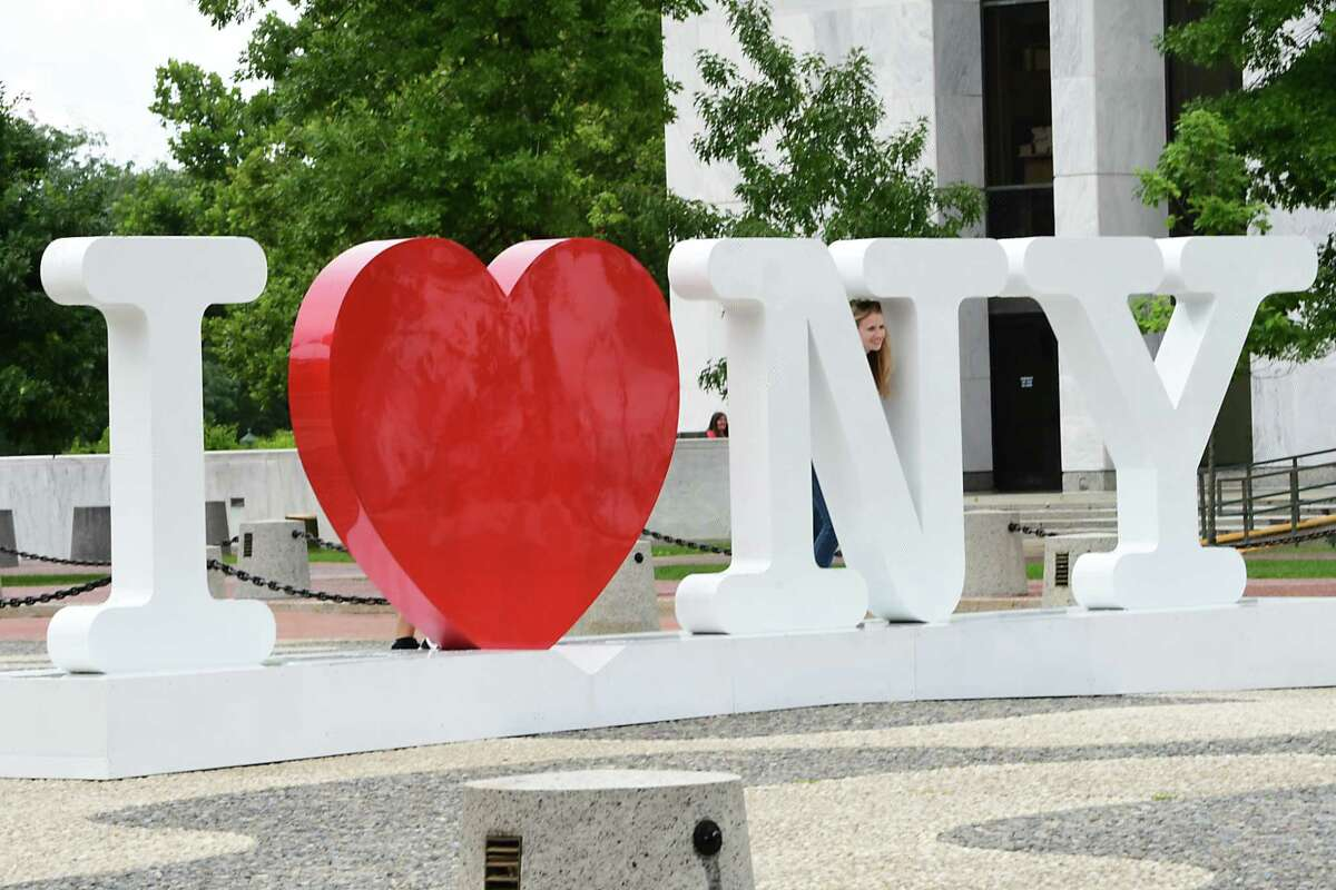 People take photos at the I love NY statue as attend the Annual New York State Food Festival at Empire State Plaza on Wednesday, Aug. 7, 2019 in Albany, N.Y. (Lori Van Buren/Times Union)