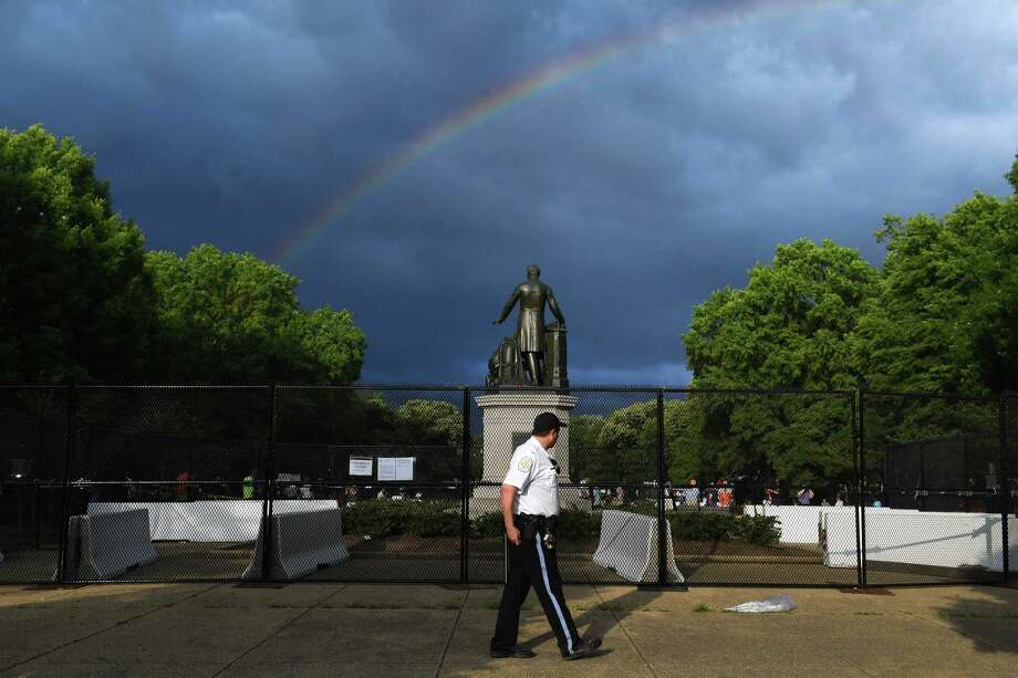 A U.S. Park Police officer is seen near the Emancipation Memorial at Lincoln Park as a rainbow appears on Thursday. Photo: Washington Post Photo By Matt McClain. / The Washington Post