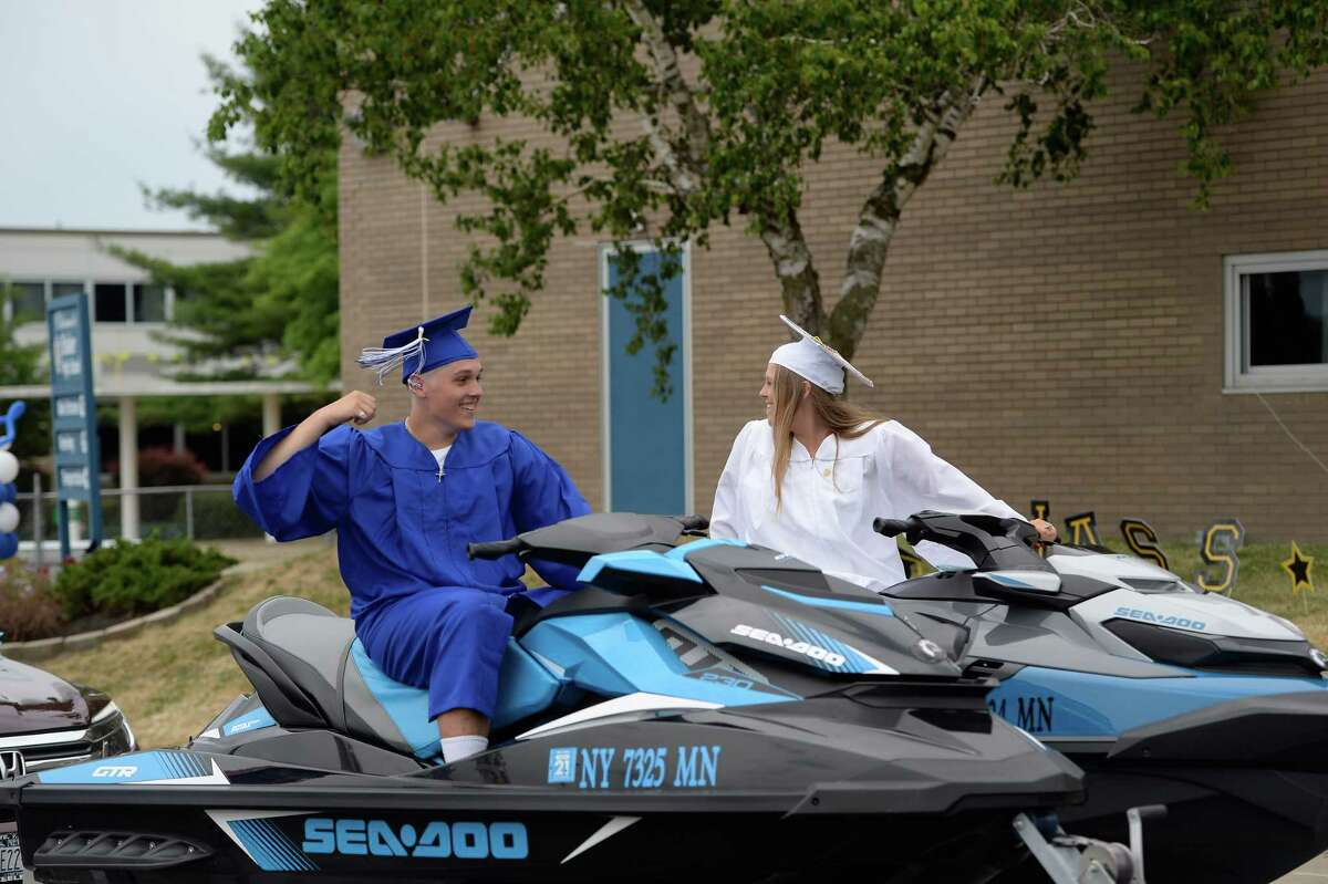 Shaker High School seniors and twins Thomas and Emelene Burek cheer as they're towed on jet skis at their school's drive-thru gradation Saturday, Jun. 27, 2020 in Colonie, N.Y. (Jenn March, Special to the Times Union )