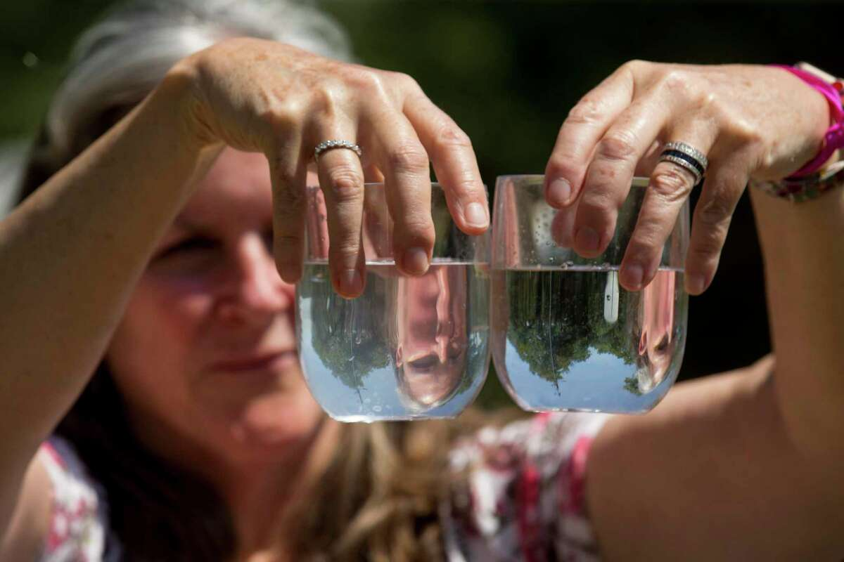 Dr. Teri Albright compares a water sample from her well, left, and compares it to a glass full of bottled water on Monday, May 11, 2020 in Blanco, Texas. After crews working for pipeline giant Kinder Morgan spilled drilling fluid during a boring operation near the Blanco River in late March, several homeowners say their wells were contaminated. Albright's well water has became contaminated.'s well water has became contaminated.