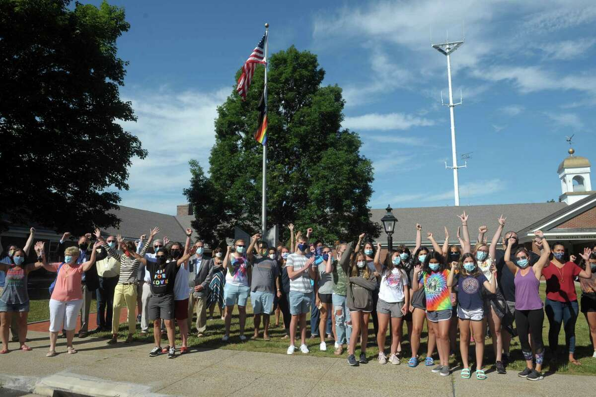 Several dozen people gathered to watch a rainbow pride flag raised in front of Town Hall, in Monroe, Conn. June 26, 2020. First Selectman Ken Kellogg also read a proclamation declaring Friday Pride Day.