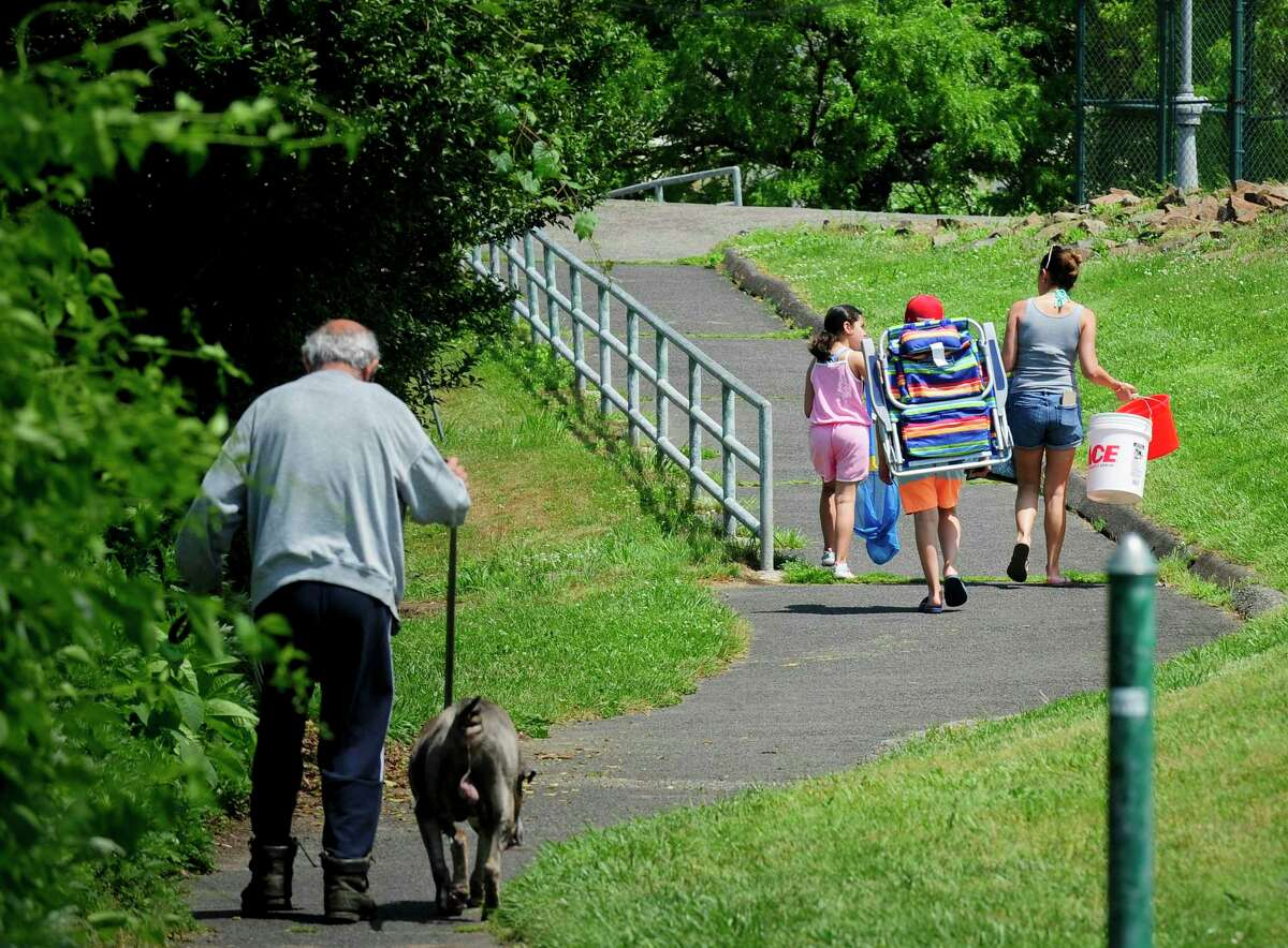 Beach goers head to West Beach after parking on a side street in the Shippan neighborhood of Stamford, Connecticut on June 6, 2020. Shippan residents are upset with all the out of towners showing up at Stamford beaches and not social distancing. in an effort to discourage non resident beach visitors, the Stamford Board of Representatives raised the out of town beach parking fee, but out of town beach goers just park on nearby streets in the Shippan neighborhood near West Beach and walk into the beaches avoiding the non resident parking fee.