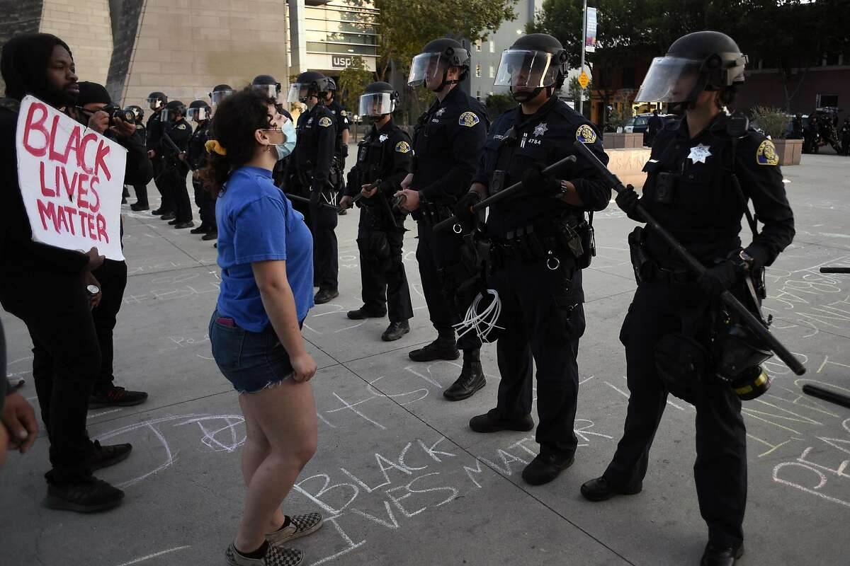 Police form a line as protesters show up at San Jose City Hall in May.