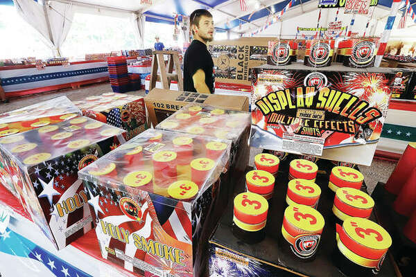 A man shopping with his family in the large shell section of the big fireworks tent behind the Gas Mart at U.S. Route 67 and Missouri Highway 94 in West Alton, Missouri, ponders the huge selection available Friday. Large sized shells, especially in multi-shell packages, are apparently selling very well this year as people decide to put on their own shows, even though it's illegal in the state of Illinois without a special permit.