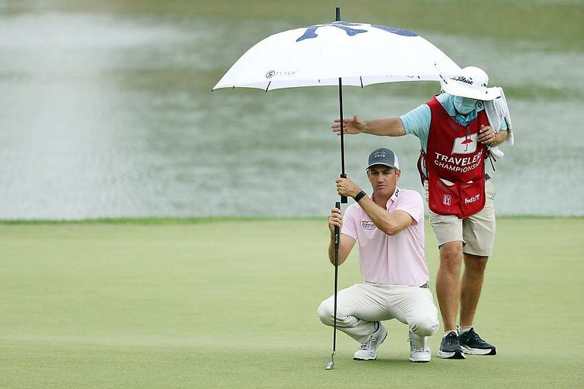 Brendon Todd balances his umbrella and his putter as he lines up a shot in the rain.