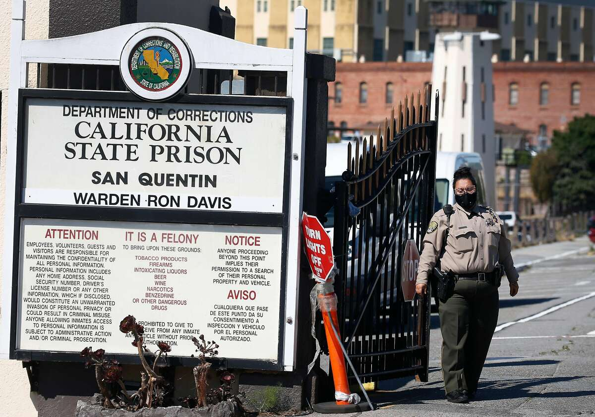 A prison guard wears a mask at the main gate to San Quentin State Prison on Thursday, June 25, 2020. Confirmed COVID-19 cases inside the prison walls have skyrocketed prompting calls for the early release of prisoners serving time for low risk crimes nearing the end of their sentence.