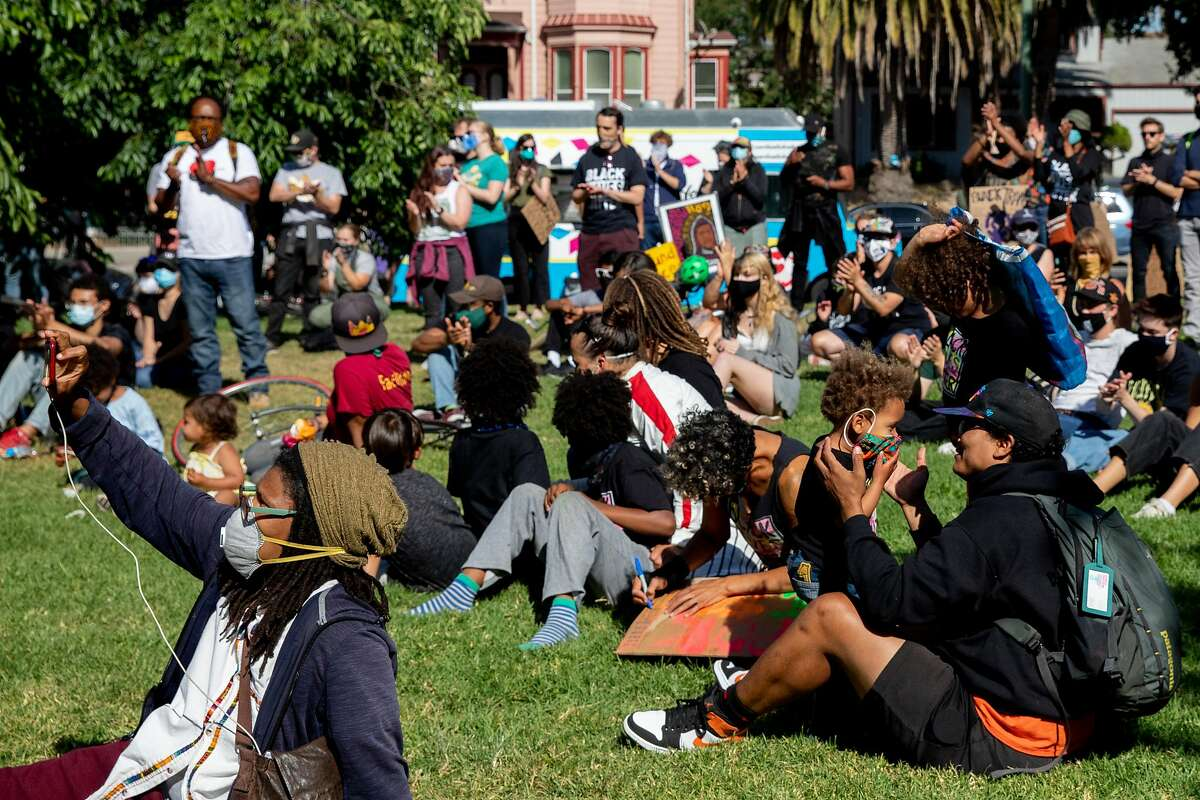 Families and demonstrators gather on the grass to listen to speakers during a youth-led Juneteenth rally and march organized by Black Youth for the People's Liberation at De Fremery Park in Oakland, Calif. Friday, June 19, 2020.