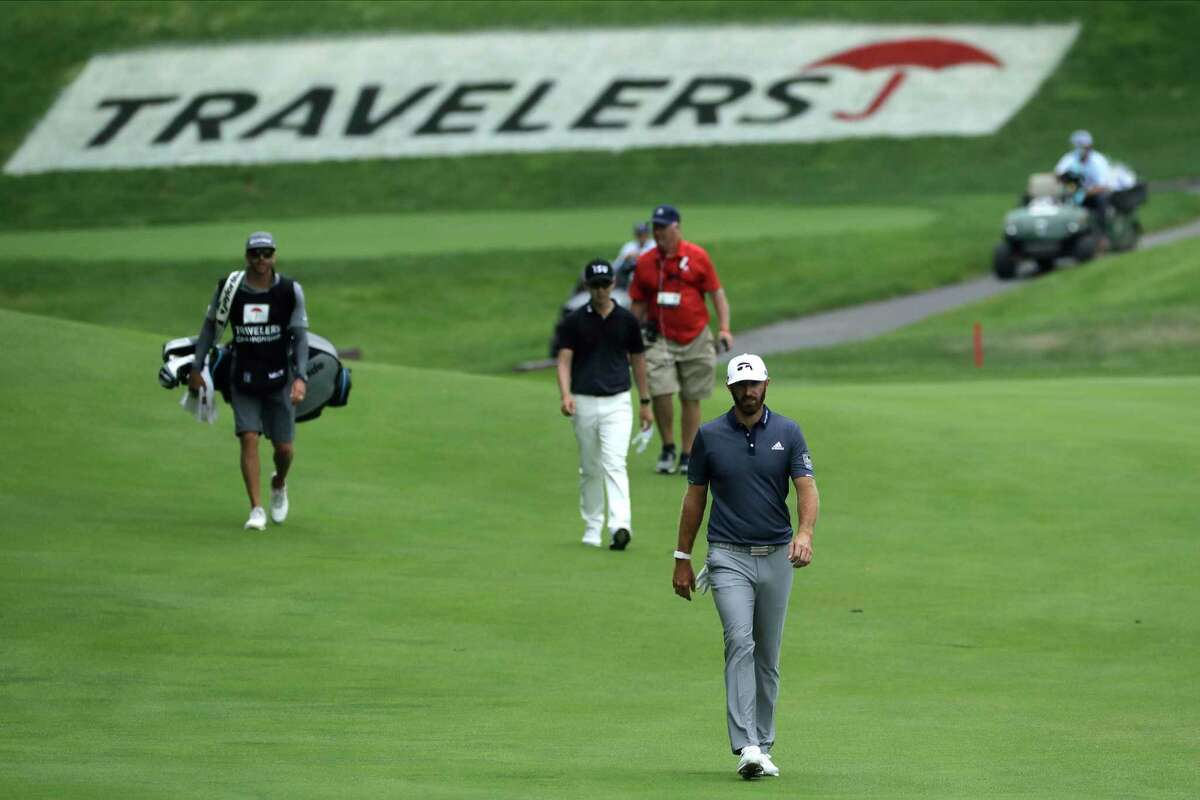 Dustin Johnson, bottom, and Seung-Yul Noh, center, of South Korea, walk up the 15th fairway during the third round of the Travelers Championship golf tournament at TPC River Highlands, Saturday, June 27, 2020, in Cromwell, Conn. (AP Photo/Frank Franklin II)