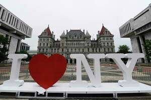 """FILE - In this Tuesday, June 18, 2019, file photo, a new promotional """"I Love NY"""" sign sits in the Empire State Plaza for installation in front of the New York state Capitol in Albany, N.Y. Milton Glaser, the designer who created the a€œI (HEART) NYa€ logo and the famous Bob Dylan poster with psychedelic hair, died Friday, June 26, 2020, his 91st birthday. (AP Photo/Hans Pennink, File)"""