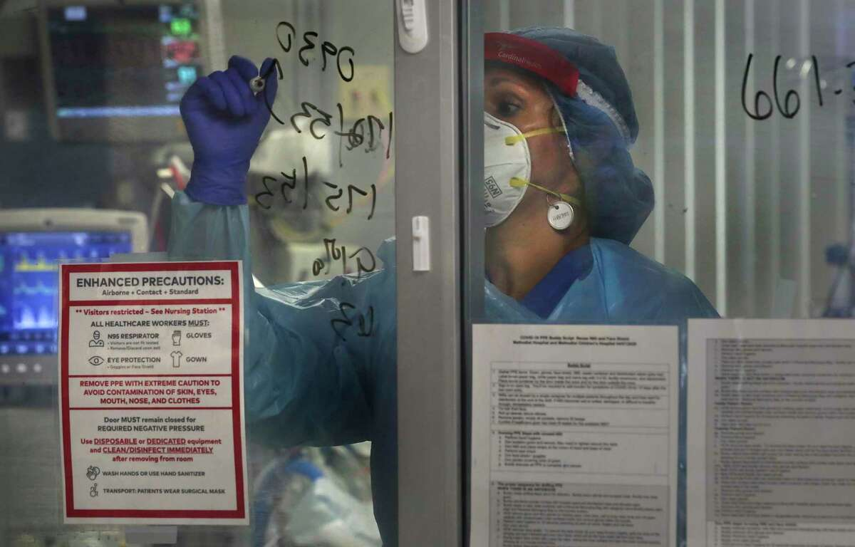 Nurse Tracie Sandoval writes details about a COVID-19 patient on a glass door to the room. Hospitals in San Antonio and other large cities in Texas are filling up with people infected by the virus. June saw record numbers of new cases emerging in the state's major cities.