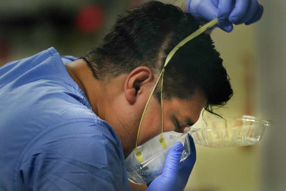 "Nurse Julio Gaona removes his N95 face mask, putting it into a ""to-go box"" to keep from contaminating surfaces at Methodist Hospital on June 25, 2020. Infection control is a major undertaking in the COVID units because the virus can spread easily."