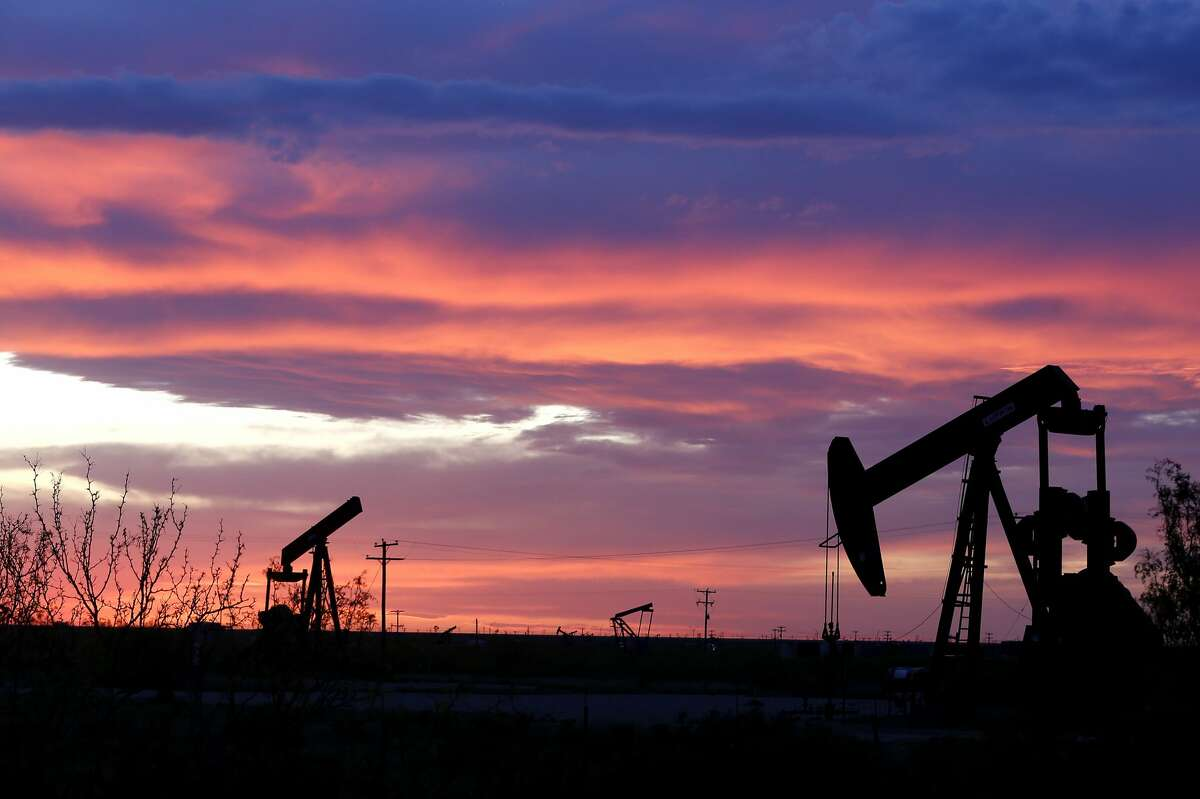 An oil pumpjack works in the field in Penwell, Texas as two others are missing their horsehead and not working on Monday, April 27, 2020.
