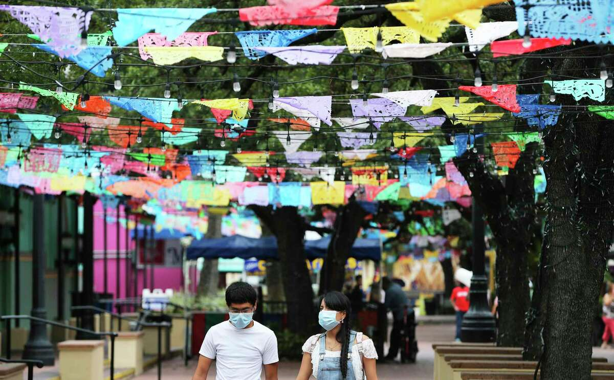 Odeli Chavarria, right, and Sonny Chhuon wear masks as they walk through Market Square on Friday. The young couple visiting from Denton had dined shopped at the mercado.
