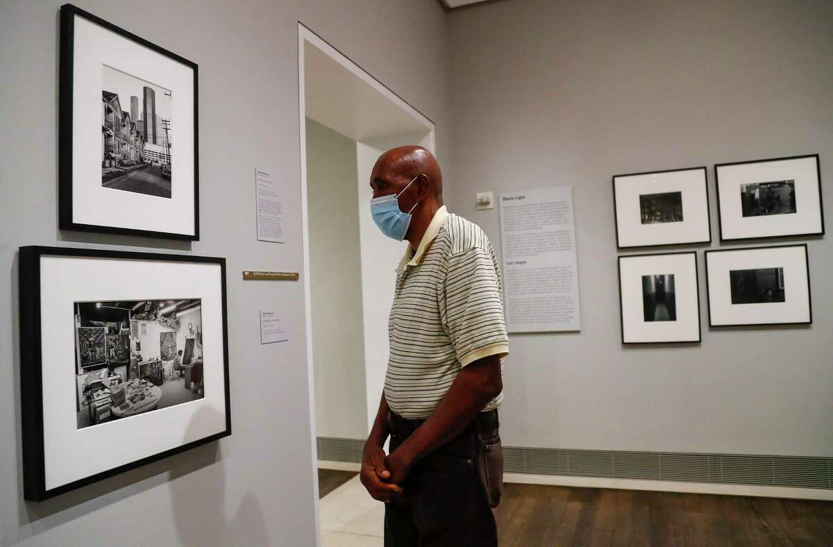 Houston photographer Earlie Hudnall, Jr. looks at two of his photographs hanging on the wall, as the exhibition Soul of a Nation opened up at the MFAH, Saturday, June 27, 2020, in Houston .